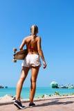 Vrouw die en een longboard lopen houden Stock Fotografie