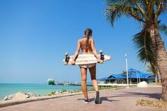 Vrouw die en een longboard lopen houden Royalty-vrije Stock Foto's