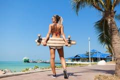Vrouw die en een longboard lopen houden Royalty-vrije Stock Afbeeldingen