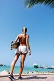 Vrouw die en een longboard lopen houden Stock Afbeeldingen