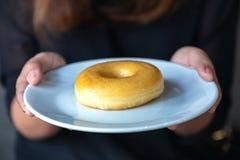 Vrouw die en een plaat van doughnut houden tonen royalty-vrije stock fotografie