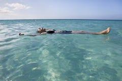 Vrouw die en in het overzees drijft ontspant Stock Foto's