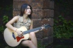 Vrouw die en het spelen gitaar situeren stock afbeeldingen