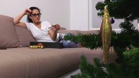 Vrouw die en Kerstmisdecoratie ontspannen controleren stock footage