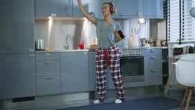 Vrouw die en in keuken zingen dansen stock video
