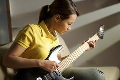 Vrouw die en met elektrische gitaar thuis spelen opleiden stock afbeelding