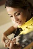 Vrouw die en met elektrische gitaar thuis spelen opleiden stock fotografie