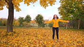 Vrouw die en onder dalende gele bladeren dansen draaien stock video