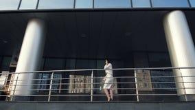 Vrouw die en op cellphone in het stads dichtbij scyscraper gebouw lopen spreken in langzame motie stock video