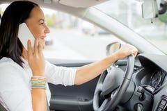 Vrouw die en op de telefoon drijven spreken Stock Afbeelding