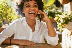 Vrouw die en op telefoon bij een koffie glimlachen spreken royalty-vrije stock foto