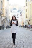 Vrouw die en slimme telefoon op stadsstraat lopen met behulp van Stock Foto