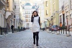 Vrouw die en slimme telefoon op stadsstraat lopen met behulp van Stock Foto's