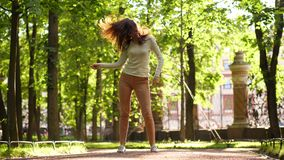 Vrouw die en in vlakkere straat, vliegend haar en tik in lucht dansen springen stock footage