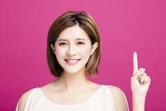 Vrouw die ergens richten aan, geïsoleerd op roze achtergrond royalty-vrije stock foto's