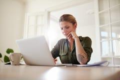 Vrouw die ernstig aan laptop thuis werken Stock Afbeelding