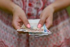 Vrouw die Euro rekening in haar handen houden Stock Afbeelding