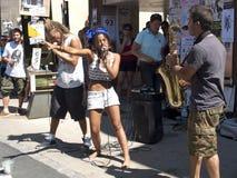 Vrouw die face to face een saxofonist zingen Stock Foto's