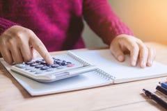 Vrouw die financiën doet en op lijst thuis bureau berekent stock foto's