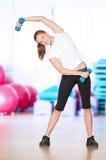 Vrouw die fitness oefening doet bij sportgymnastiek Stock Afbeeldingen