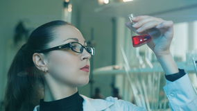 Vrouw die fles in een laboratorium onderzoeken stock footage