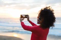 Vrouw die foto met mobiele telefoon nemen tegen het overzees stock fotografie