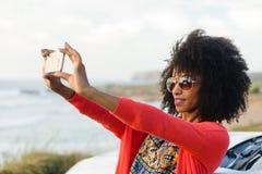 Vrouw die foto met mobiele telefoon nemen tegen het overzees royalty-vrije stock afbeeldingen