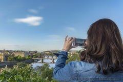 Vrouw die foto's met telefoon in Praag nemen Stock Afbeeldingen