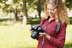 Vrouw die foto's nemen terwijl status in het park royalty-vrije stock afbeelding
