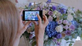 Vrouw die foto van grote bloemenmand met bloemen met smartphone nemen stock video