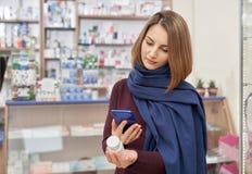 Vrouw die foto van pillenfles nemen in drogisterij stock foto