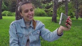 Vrouw die foto van zich met smartphone in het park nemen stock footage