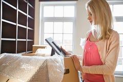 Vrouw die fotokader bekijken terwijl het uitpakken van bewegende dozen bij nieuw huis royalty-vrije stock fotografie