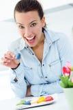 Vrouw die Franse koekjes thuis eten stock foto's