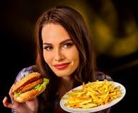 Vrouw die frieten en hamburger op lijst eten Stock Foto's