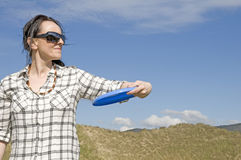 Vrouw die frisbee in zandduinen werpt Royalty-vrije Stock Foto's