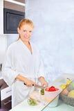 Vrouw die fruitsalade in keuken maakt Stock Foto