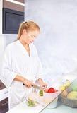 Vrouw die fruitsalade in keuken maakt Stock Afbeeldingen