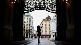 Vrouw die gadget in hofburg Wenen, silhouet, brede hoek gebruiken royalty-vrije stock afbeeldingen