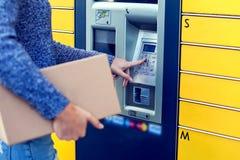 Vrouw die geautomatiseerd zelfbedienings post eindmachine of slot gebruiken stock foto's