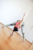 Vrouw die geavanceerde yoga uitoefenen tegen een heldere muur Stock Afbeelding