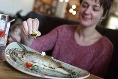 Vrouw die gebraden forel eten royalty-vrije stock afbeeldingen