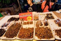 Vrouw die gebraden sprinkhanen en eetbare insectlarven verkopen bij traditionele Thaise nachtmarkt Stock Afbeeldingen