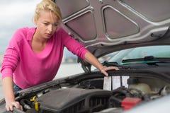 Vrouw die gebroken motor van een auto inspecteren Stock Foto