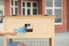 Vrouw die gebruikte plastic fles werpen in het recycling van bak op straat stock foto's