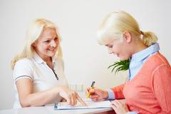 Vrouw die geduldige vormen invullen bij tandarts Stock Foto's