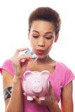 Vrouw die geld in spaarvarken zetten stock afbeeldingen