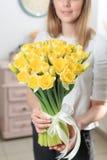 Vrouw die gele narcissen houden Mooi boeket van de lentegele narcissen in haar handen als gift royalty-vrije stock fotografie