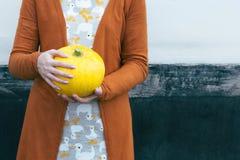 Vrouw die gele pompoen in handen houden Stock Foto's
