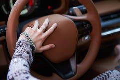 Vrouw die gele sportwagen met het stuurwiel van de handgreep drijven royalty-vrije stock foto's